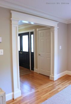 Decorative molding added to standard doorways makes such a huge difference!: Columns Ideas, Living Rooms, Moldings Ideas, Decor Moldings, Foyers Kitchens, Front Doors, Standards Doorway, Huge Difference, Crowns Moldings