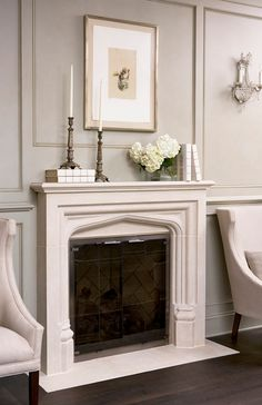 The fireplace is carved limestone and it's by Francois & Co. These sconces are antique and the chairs are by Hickory White.