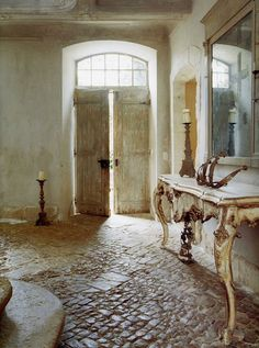"shades of cream and ivory, disorganized brick floors, distressed walls, rustic double doors with no side windows, distressed entry table and large colonial style mirror...wow. ""A great example where rustic meets glamour in this French interior by Francois and Michelle Joubert.....The Chateau de Gignac"""