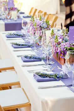 Decoracion con camino de mesa y servilletas de color lila.