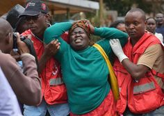 Members of the Red Cross help a relative of one of the students massacred by Shebab Islamists at a Kenyan university, at a funeral parlour in Nairobi, on Apr...