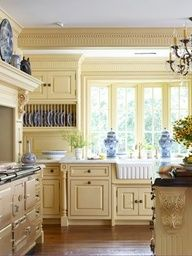 Pale Yellow Kitchen Cabinets Kissed With Blue    @Liesal Hoffman This is my favorite so far... yellow on the walls with blue art or a blue buffet/hutch.