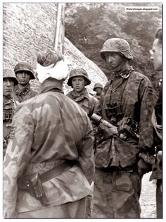 Waffen SS Colonel Max Wunsche, commander of the 12th SS Regiment of the Hitlerjugend Division (bandaged head) with men of the 25th regiment of the SS at Po (village in France) on June 9, 1944. Partly seen on the right side of the image is Rudolf, son of German foreign minister von Ribbentrop.