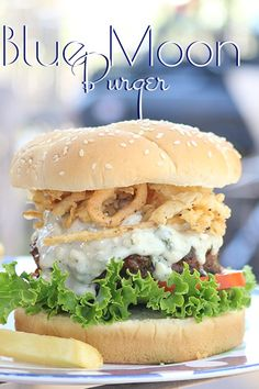 Blue Moon Burger – the ultimate comfort food; seasoned beef topped with a chunky, creamy blue cheese blend adorned with lettuce, tomato, fried onions and a toasted bun.