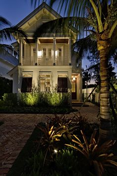 Beach cottage at dusk framed by a palm and lighting to emphasie the welcoming…