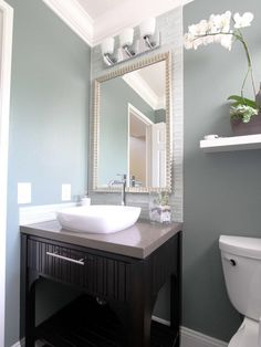 In this soothing blue-gray and white contemporary bathroom, small details add visual texture, such as the framed mirror, the white glass-tile backsplash, the vessel sink and the textured dark wood vanity.