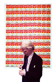 1962 - Andy Warhol in front of his tomato soup painting, 100 Cans.