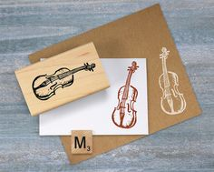 This listing is for for one hand carved Violin stamp. This original design music stamp is designed in a woodcut style and is perfect for music lovers, students, and teachers. Use this instrument stamp for all of your paper craft and memory projects including card making, scrapbooking, art journaling, gift wrap or any other project. Stamped image size 2.25 x 1 inches (wood size may vary from that shown in the picture)  Each stamp is carved individually out of soft block carving material and…