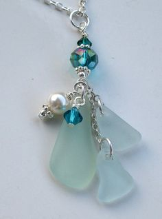 "Sea Glass Necklace Three (3) pieces of perfectly frosted aqua sea glass dangle beneath aqua Swarovski crystals. This stunning sea glass pendant measures approximately 2"" and is mounted onto a Sterling Silver necklace measuring 17"" long."