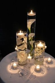 Because I know shelly loves cala lillies!!        Love the submerged white orchids and cala lillies with floating candles. Candle votives and crystals spread lightly on the table finish the look. I would prefer doing one tall centerpiece alternating between lillies and orchids on each table.