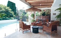 Swimming pool goals: inspiration for at-home summer relaxation: Bamboo and beam ceiling, an Indian weaving table used as a coffee table, a Bamileke stool and a woven leather lounge seat from the Philippines give an exotic feel to the 1930s Spanish-style home of South Africa interior designer Serena Crawford.