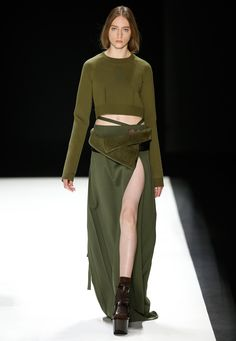 LOOK 27. Olive silk knit cropped sweater with pinstriped panel at back. Olive wool maxi kilt with pleated back and side front slit. Black and olive sheepskin waist gaiter.