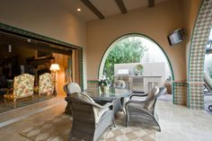 Indoor outdoor living patio surrounded by archways to the yard