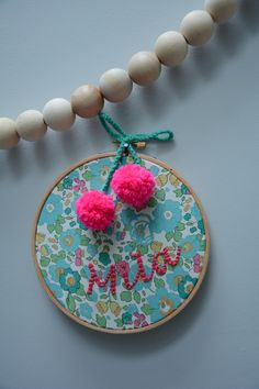 Broderie dans un cercle à broder, tissu Liberty Betsy turquoise, pompons rose