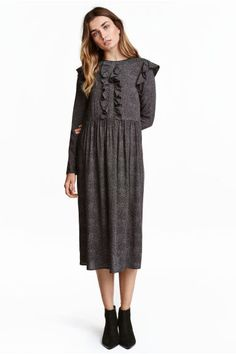 Patterned dress: Dress in a patterned viscose weave with long sleeves and a decorative frill on the front and shoulders. Opening with a button at the back of the neck, a seam at the waist and flared skirt. Unlined.