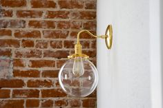Beautiful brass sconce with 8 clear glass globe. Can be installed pointing up or down. Handmade in the U.S.A. with top quality solid brass components. Features an on/off switch on the side of the socket. Other globes available in the sconce section of the shop. Canopy is 5 in diameter. Globe is 8 in diameter. 10 from the outside of the globe to the wall (depth) and 15 from the top of the canopy to the bottom of the globe, interior clearance is 2.25. Takes a standard medium base bulb up t...