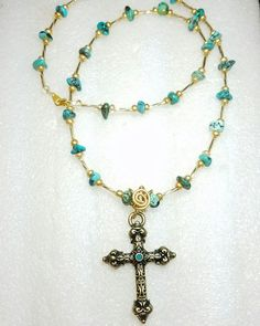 Gold and turquoise beads handmade necklace with a brass colored cross with green center.