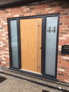 The Ancona Solid Solidor composite door with an anthracite grey frame and Irish Oak door including bespoke side panels and brushed aluminium hardware. Installed in West Bridgford, Nottingham. Dark Front Door, Timber Front Door, Composite Front Door, Best Front Doors, Main Door Design, Front Door Design, Window Design, Modern Entrance Door, Front Door Entrance