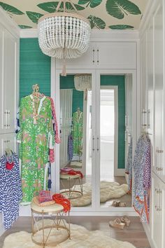 Glamorous white and green closet is clad in green grasscloth wallpaper complementing a palm leaf wallpapered ceiling holding a white beaded chandelier over a gold stool placed on a white sheepskin rug. Palm Leaf Wallpaper, Wallpaper Ceiling, Grey Wallpaper, Wallpaper Ideas, Wardrobe Doors, Built In Wardrobe, Wardrobe Design, Wardrobe Ideas