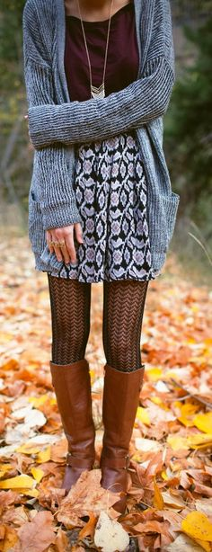 Gray knit cardigan, burgundy t-shirt, black and white patterned skirt, black chevron pattern tights, and brown boots.