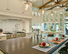 Glass door cabinets, globe lights, wood beams, large island for workspace, seating and entertainment