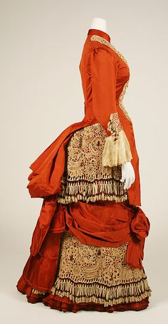 Haute Couture Victorian fashion dress gown from American 1880, 19th century #Historical #Costume. Made from silk with cotton crochet flower floral ivory lace and fringe beaded with red glass bead. Ruched and gather design with high neck, front button and a long sleeve creates a decorative effect emphasizes the bodice, waistline and the pleated hem. Full hips are enhanced by a puffed bow.The bustle at the back of the skirt flow into a graceful train. #Hautecouture #Vintage #Victorian #Fashion