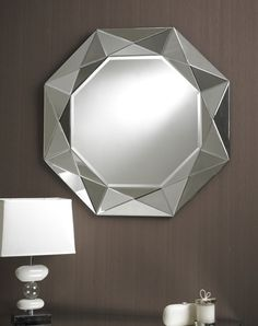 This contemporary round mirror features a 3D style border made up of triangular reflective glass sections making pyramid shapes; the different angles give an interesting geometric multi-facet effect to the border.