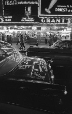 Times Square, New York, with the neon lights brilliantly reflected by the passing cars.  Photo: Harold Feinstein, 1957.
