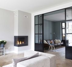 Modern living room idea with dark glazed sliding doors and corner fireplace Living Room Interior, Home Living Room, Living Area, Living Spaces, Style At Home, Sala Grande, Interior Styling, Interior Design, Home Fireplace