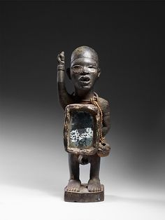 Power Figure: Standing Male with Raised Arm (Nkisi) Artist: Master of Kasadi Workshop Date: 19th–early 20th century Geography: Democratic Republic of the Congo; Republic of the Congo; Cabinda, Angola Culture: Kongo peoples; Yombe group Medium: Wood, metal, mirrored glass, resin Dimensions: H. 13 in. (33 cm), W. 4 3/4 in. (12 cm), D. 4 3/8 in. (11 cm)