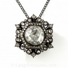 This spectacular vintage bauble beams bright and beautiful with a scintillating rose-cut diamond, with an estimated weight of 3 carats, and the dimensions of a 6-7 carat modern-cut stone. Crafted in darkened silver over 18K rosy gold, this unique jewel most likely originates from early-to-mid-twentieth century Holland, where they specialized in emulation of 18th century English-Georgian jewels. 1 1/8 inches from point to point.