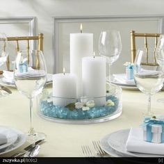 Something like this with the pillar candles, except our theme colored sea glass+sea shells+ starfish
