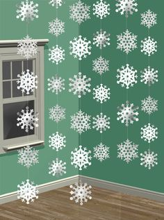 Snowflake chains hanging down from the top of a solid colored backdrop....