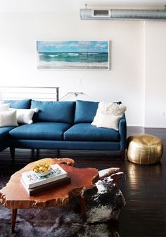 Birch+Bird Vintage Home Interiors. love everything in this room: exposed duct work, seascape photo, blue couch, gold pouf, woodcut table and animal throw.