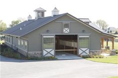 Horse barn...Love the doors, stone trim and overhang. Plus cupolas!