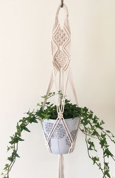 This macramé plant hanger has been carefully knotted using unbleached cotton. Its a versatile style that can be hung from a hook in the ceiling or against a wall like a wall hanging. The hanger is made using a series of macramé knots and a pot or glass globe sits neatly amongst it, in the pictures I have used two pots, the largest measuring 13 cms In height X 15 cms in diameter. The hanger could be heavy depending on the weight of your chosen plant and pot so please ensure your fixings are…