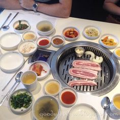 삼겹살  Sam gyeop sal - thick bacon (pork belly) grilled at the table with onions and garlic, served with banchan (side dishes)
