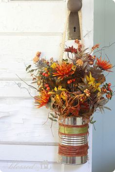 Decorate a tin can with ribbons in fall colors, creating the perfect vase for an arrangement of pretty blooms.