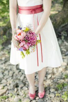 knielanges hochzeitskleid mit schwingendem rock und rosa- rotem gürtel mit schleife und bändern zum binden, v- ausschnitt mit breiten trägern, fascinator, runde brautschuhe emma in rosa gefärbt (Foto: Hanna Witte) (http://www.noni-mode.de)