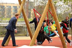 Popular Prince: Mayor of London Boris Johnson watches as Prince Harry pushes school children on a swing during a visit to the new Queen Elizabeth Olympic Park