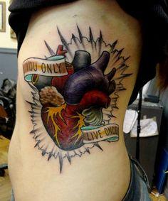 Tatouage old school organe coeur sur le coté d'une fille https://tattoo.egrafla.fr/2016/02/19/modeles-tatouage-coeur/