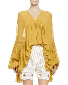 Chloe crinkled sheer crepe blouse in allover ruffles. V neckline. Full sleeves with ruffled lantern cuffs. Flowing silhouette. Mustard Yellow sheer full flounced top. Arched hem dips at sides; cropped at front.Full-Sleeve Flounce Blouse, by Chloe