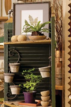 By hinging two vintage shutters together, a corner shelf was created. Horizontal shelves were added, and S hooks allow for hanging items.