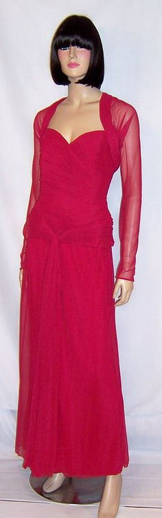 This is an ultra-glamorous and form fitting creation in a larger size, 42 EU and 10 US, designed by Vicky Tiel for Bergdorf Goodman. The gown is strapless and has a heavily ruched, fitted bodice, a back zipper for closure, and a flowing full length skirt. It also has a lively long sleeved bolero jacket with a ruched collar which gives the gown an extra touch of elegance. It is in excellent vintage condition.