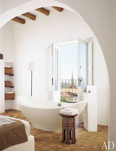 In this 300-year-old summer retreat reinvented by architect James Cavagnari for himself and his wife, designer Erin Quiros, the bathroom is anything but ordinary. The space features a freestanding tub, snow-white plaster walls, and a rustic beamed ceiling; the French doors frame a stunning view of the Sicilian coast.