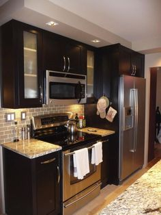 espresso cabinets with stainless steel appliances and backsplash....love this for when we redo kitchen countertops ccc: