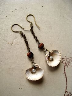 These extremely delicate earrings were made with the seashells I picked from the shore of Baltic sea last summer. The shells dangle on a brass chain and are topped by a wire wrapped mocha brown pearl. There is also a white pearl dangle inside of each seashell. These earrings measure