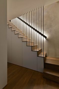 These modern wood stairs have a handrail with hidden lighting, and a floor-to-ceiling steel rod safety barrier. Square Feet Architects have designed modern stairs that have handrails with hidden lighting, and floor-to-ceiling steel rods safety barriers. Wood Stair Handrail, Staircase Railings, Wood Stairs, House Stairs, Staircase Ideas, Basement Stairs, Handrail Ideas, Black Staircase, Timber Staircase