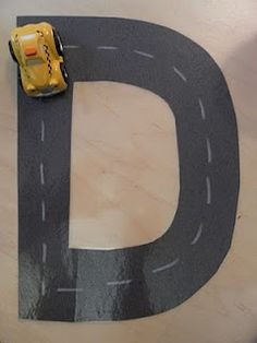 Driving a toy car on Road Letters, getting to know letters/ prewriting practice.