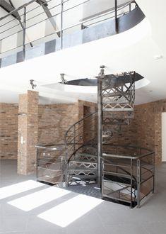 Photo DH88 - SPIR'DÉCO® San Francisco. Escalier hélicoïdal d'intérieur sur 2 niveaux en acier au design industriel pour une décoration de caractère. Marches Nanoacoustic® tôle striée pour un escalier tout métal silencieux. Contremarches et limon découpés façon charpente à l'ancienne avec rivets forgés. Finition : acier brut patiné. - Modèle déposé Escaliers Décors® - © Photo : Nicolas GRANDMAISON